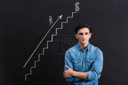 Photo for Confident young man with crossed arms and blackboard with startup and business growth drawing - Royalty Free Image