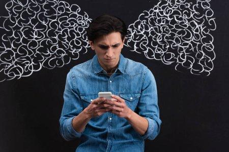 Photo pour Jeune homme concentré à l'aide d'un smartphone, avec de la vapeur des oreilles dessinée sur un tableau - image libre de droit