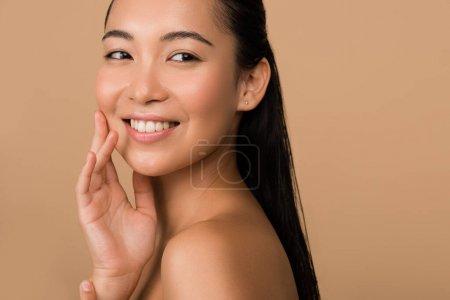 Photo pour Belle fille asiatique souriante, nue, regardant loin isolée sur beige - image libre de droit