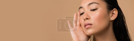 Photo for Beautiful asian girl touching face isolated on beige, panoramic shot - Royalty Free Image
