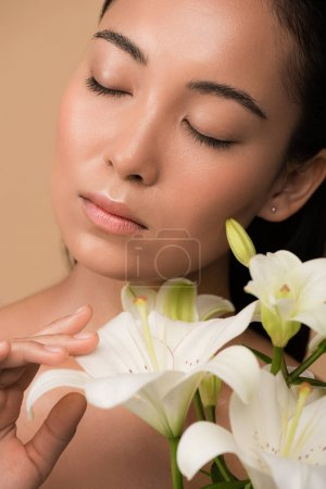 beautiful naked asian girl with closed eyes and white lilies isolated on beige