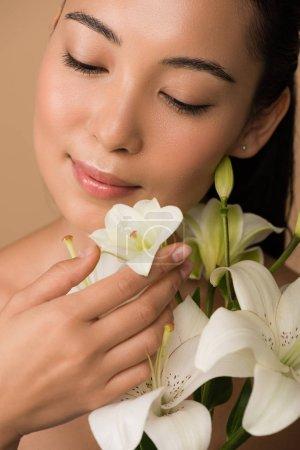 Photo pour Sourire belle fille asiatique nue avec les yeux fermés et des lis blancs isolés sur beige - image libre de droit