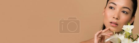 dreamy beautiful naked asian girl with white lilies isolated on beige, panoramic shot