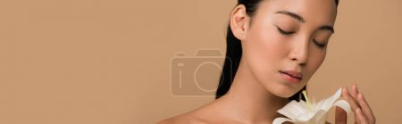 beautiful naked asian girl with closed eyes holding white lily isolated on beige, panoramic shot