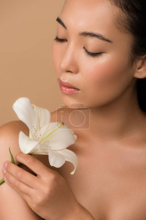 beautiful naked asian girl holding white lily isolated on beige