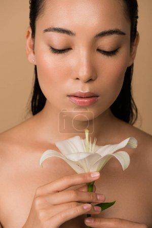 Photo pour Belle nu asiatique fille regarder blanc lis isolé sur beige - image libre de droit
