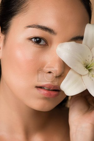 beautiful naked asian girl holding white lily near face isolated on beige