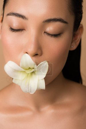 Photo for Beautiful naked asian girl with closed eyes holding white lily in mouth isolated on beige - Royalty Free Image