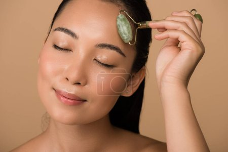 Photo for Smiling beautiful naked asian girl with closed eyes massaging face with jade roller isolated on beige - Royalty Free Image