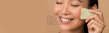 Photo for Smiling beautiful asian girl with closed eyes using facial gua sha jade board isolated on beige, panoramic shot - Royalty Free Image