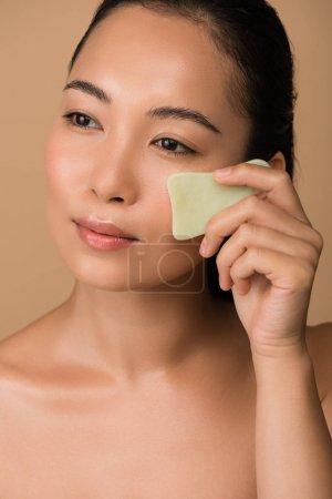 Foto de Hermosa chica asiática desnuda usando pizarra de agua facial sha tabla aislada en beige. - Imagen libre de derechos
