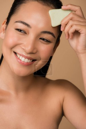 Photo for Smiling beautiful naked asian girl with closed eyes using facial gua sha jade board isolated on beige - Royalty Free Image