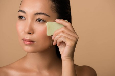Photo for Beautiful naked asian girl using facial gua sha jade board isolated on beige - Royalty Free Image
