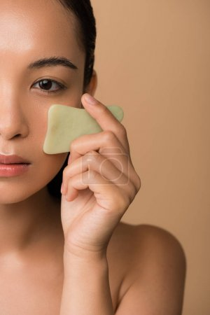 Photo for Cropped view of beautiful naked asian girl using facial gua sha jade board isolated on beige - Royalty Free Image