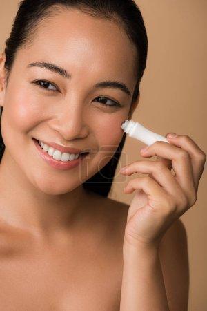 Photo pour Belle fille asiatique souriante et nue utilisant un rouleau à œil isolé sur beige - image libre de droit