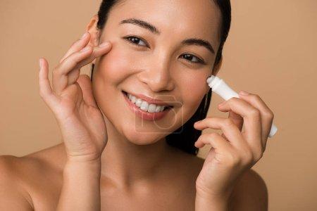 Photo pour Sourire belle nu asiatique fille en utilisant oeil rouleau isolé sur beige - image libre de droit