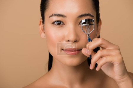 Photo pour Beautiful naked asian girl using eyelash curlers isolated on beige - image libre de droit