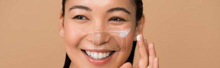 Photo pour Heureux belle asiatique fille application visage crème isolé sur beige panoramique shot - image libre de droit