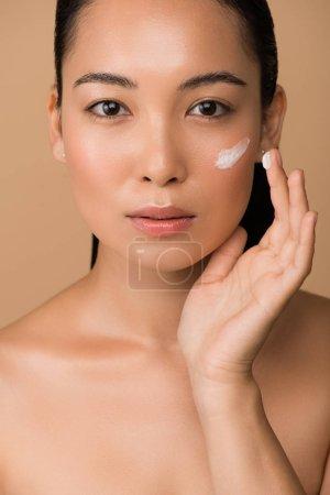 Photo pour Belle fille asiatique nue appliquant de la crème faciale isolée sur beige - image libre de droit