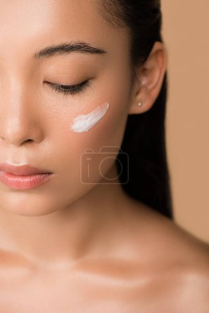 Photo for Cropped view of beautiful naked asian girl with facial cream on cheek isolated on beige - Royalty Free Image