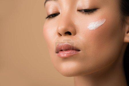 Photo pour Belle asienne avec crème faciale sur joue isolée sur beige - image libre de droit