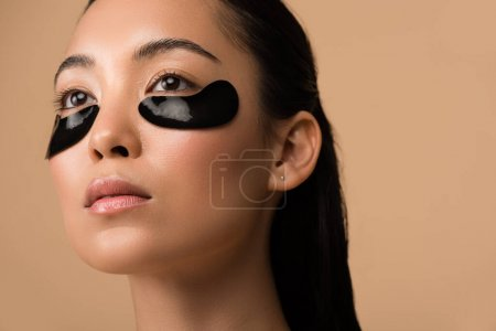 Photo for Beautiful asian girl with black hydrogel eye patches under eyes isolated on beige - Royalty Free Image