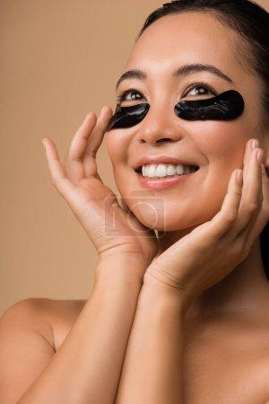 Photo pour Sourire belle nu asiatique fille avec noir hydrogel oeil patchs sous yeux isolé sur beige - image libre de droit