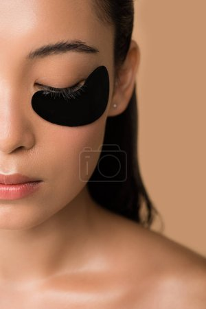 Photo for Cropped view of beautiful naked asian girl with black hydrogel eye patch under closed eye isolated on beige - Royalty Free Image