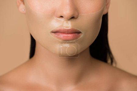 Photo for Cropped view of beautiful naked asian girl with closed eyes and hydrogel mask on face isolated on beige - Royalty Free Image