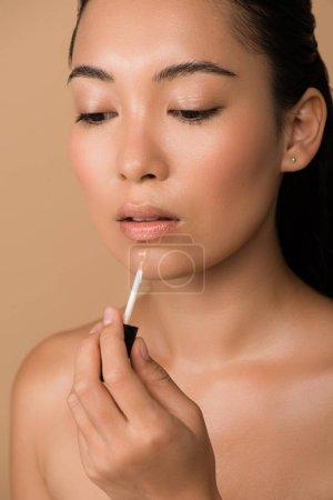 Photo pour Belle nu asiatique fille application lèvre brillant sur lèvres isolé sur beige - image libre de droit