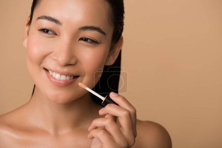 Photo for Smiling beautiful naked asian girl appying lip gloss on lips isolated on beige - Royalty Free Image