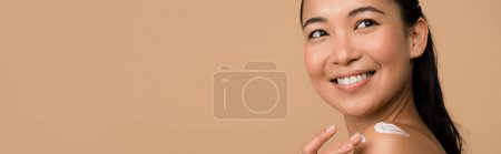 Photo for Smiling beautiful naked asian girl with cosmetic cream on shoulder isolated on beige, panoramic shot - Royalty Free Image