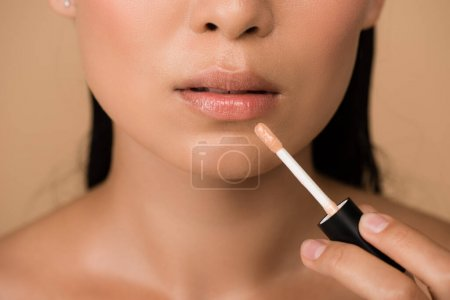 Photo pour Cropted view of beautiful naked asian girl appying lip gloss on lips isolated on beige - image libre de droit