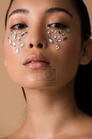 Photo pour Belle fille asiatique nue avec des pierres tombales sur le visage isolée sur beige - image libre de droit