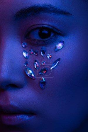 Photo pour Vue rapprochée de belle fille asiatique avec strass sur le visage en lumière bleue - image libre de droit