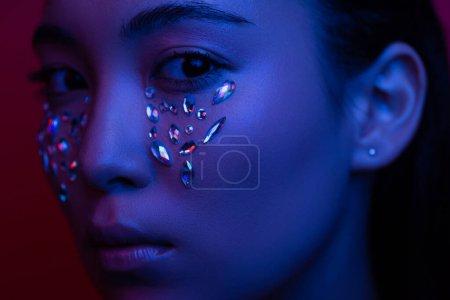Photo pour Belle fille asiatique avec strass sur le visage dans la lumière bleue - image libre de droit
