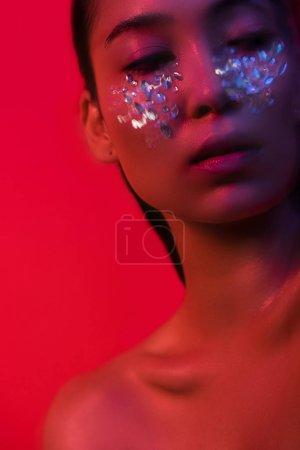 Photo pour Belle fille asiatique nue avec strass sur le visage isolé sur rouge, flou de mouvement - image libre de droit
