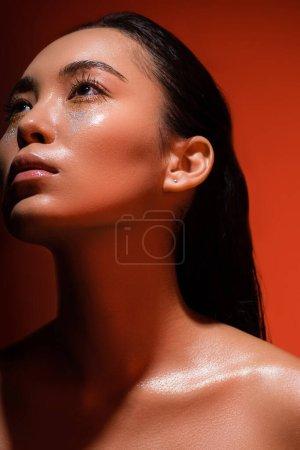 Photo pour Bas angle vue de belle nu asiatique fille avec argent scintille sur visage sur rouge - image libre de droit