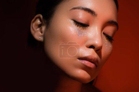 Photo pour Belle asiatique fille avec argent scintille sur visage et fermé les yeux sur rouge et noir - image libre de droit