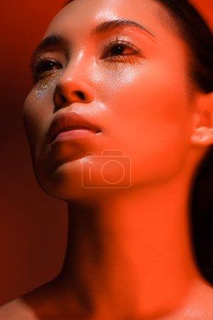 Photo pour Vue à angle bas de belle fille asiatique nue avec de l'argent scintille sur le visage dans l'éclairage rouge - image libre de droit