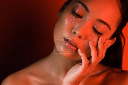 Photo pour Belle fille asiatique nue avec des scintillements argentés sur le visage et les yeux fermés dans un éclairage rouge - image libre de droit