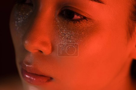 Photo pour Vue rapprochée de belle fille asiatique avec de l'argent scintille sur le visage dans l'éclairage rouge - image libre de droit