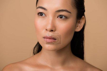 Photo pour Belle fille asiatique nue regardant loin isolée sur beige - image libre de droit