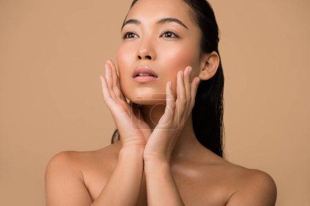 Photo pour Belle fille asiatique nue se touchant le visage et regardant loin isolée sur beige - image libre de droit
