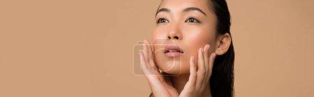 Photo pour Belle asiatique fille toucher visage et regarder loin isolé sur beige, panoramique coup - image libre de droit