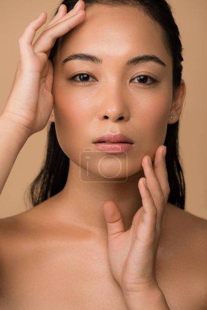 Photo pour Belle fille asiatique nue touchant le visage isolée sur beige - image libre de droit