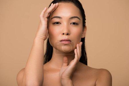 Foto de Hermosa chica asiática desnuda que toca la cara aislada en beige. - Imagen libre de derechos
