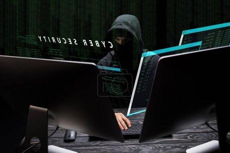 Photo pour Pirate dans le masque assis près des moniteurs d'ordinateur et le lettrage de cybersécurité sur noir - image libre de droit