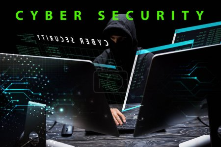 Photo for Hacker in hood sitting near computer monitors near cyber security lettering on black - Royalty Free Image
