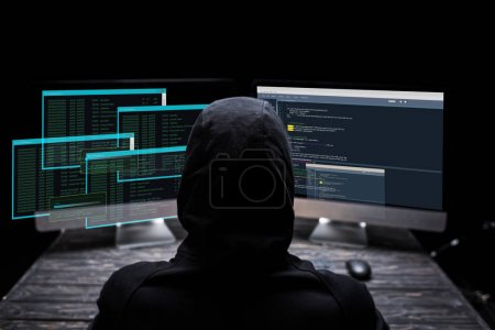 Photo for Back view of hooded hacker sitting near computer monitors with data on screens on black - Royalty Free Image